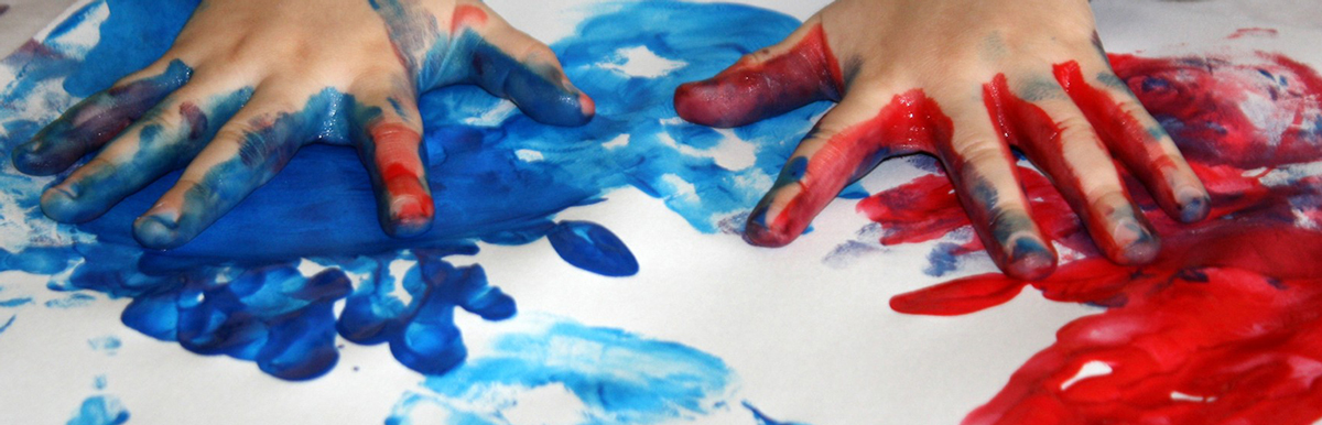 Student Finger Painting with Red and Blue